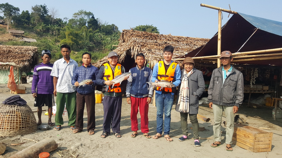 FISHBIO staff holding fish near the Chindwin River in Myanamr