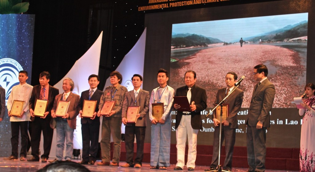 Sinsamout (fourth from left) with his prize-winning photo displayed