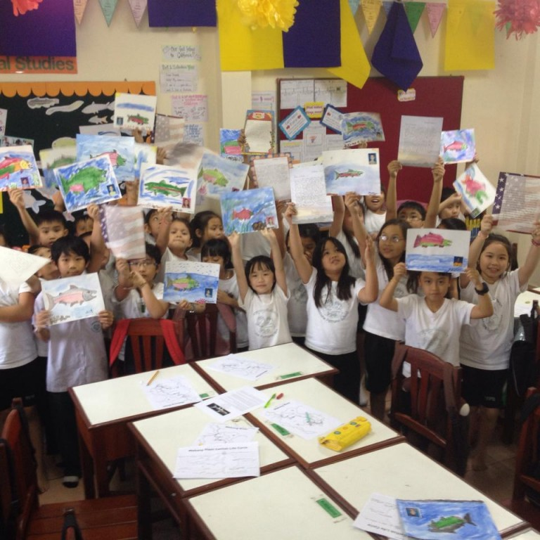 Lao students show letters and salmon drawings they received from California