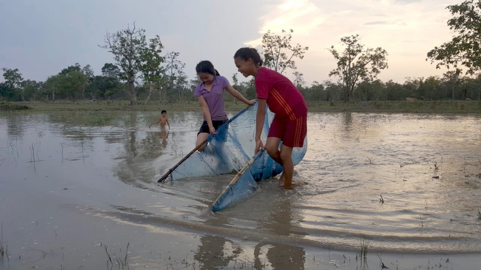 Two Lao girls harvesting aquatic invertebrates