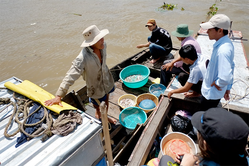 University researchers (right) buy fish for their survey from a local fisherman (left).